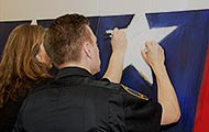 Guests at the Hometown Hero unveiling write their hero messages on the canvas