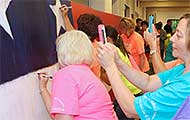 Volunteers and attendees of Hometown Hero unveiling write messages on the interactive exhibit