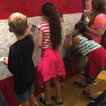 Children writing hero messages on Hometown Hero at ArtPrize Seven