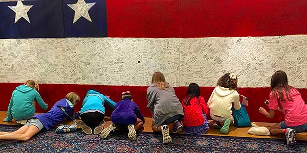 Row of young girls writing hero messages on Hometown Hero at ArtPrize Seven