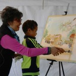 A young visitor gets some hands on experience with watercolor painting