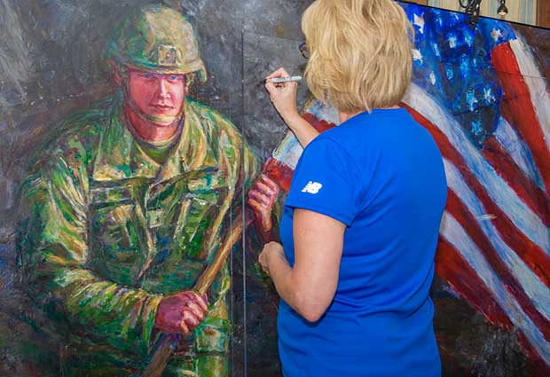 Blue Star Mother writes hero message on Hometown Hero II at unveiling ceremony