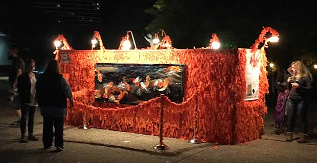 Night scene of Color Me Orange—Color Me Kind full of orange ribbons tied on by ArtPrize visitors