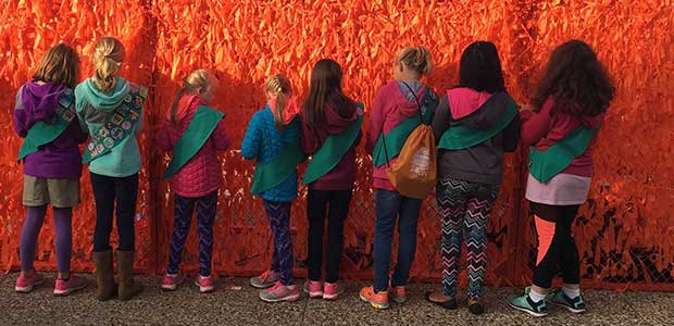 Orange ribbons being tied on to Color Me Orange—Color Me Kind at ArtPrize Eight