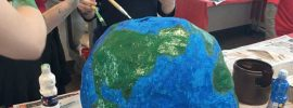 Students painting a paper mache globe
